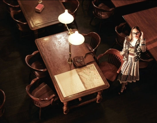 Jacket and skirt by Victoria Beckham; top by Sibling; collar by Michael Kors Collection; glasses by Cutler and Gross; earrings by Erickson Beamon; sandals by Miu Miu; bag (on table) by Gucc